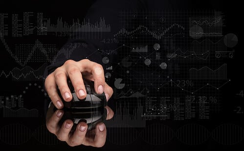 Hand using wireless mouse with financial concept on dark background