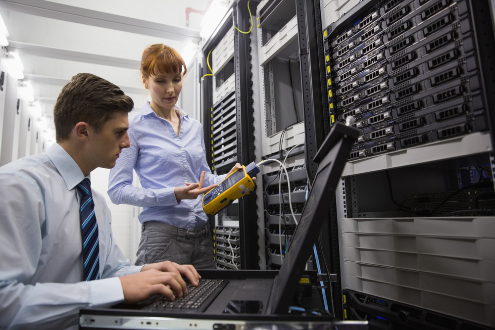 Team of technicians using digital cable analyser on servers in large data center-1