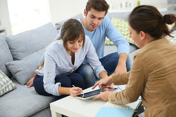 Young couple signing financial contrat on digital tablet-1